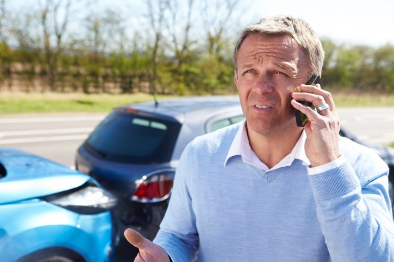 28154970 - driver making phone call after traffic accident